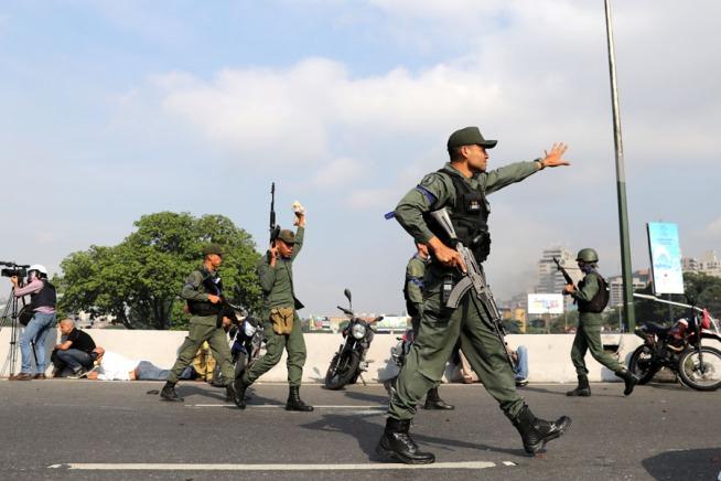 Military members gesture near the Generalisimo Francisco de Miranda Airbase in Caracas